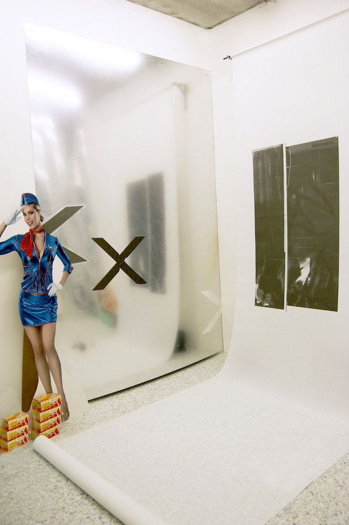 Screen print on terylene sailcloth, steel bracket, acrylic on mirrored Perspex, life-size Air Hostess cut out, karaoke light, screen printed chip boxes, underlay flooring, 'Shoe Zone' paintings, spot lights, foil balloons, flowers, mirror film, 'Richard Branson', camera & tripod, dimensions variable, 2015.